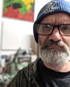 Photo of grumpy looking artist with blue hat, glasses and beard in shed facing directly into camera